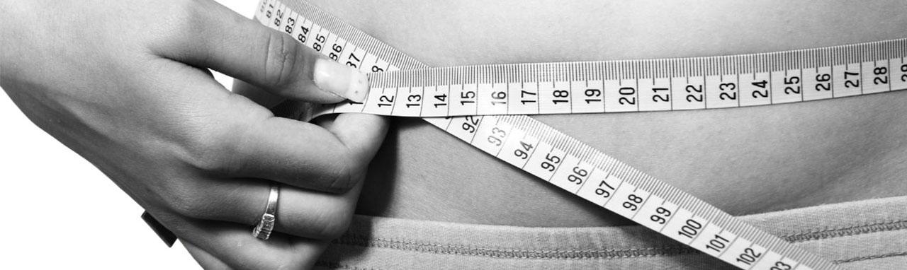 Une femme mesure son tour de taille avec un mêtre ruban