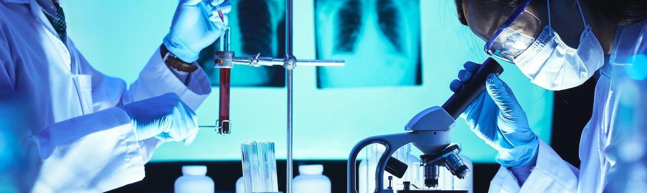 Deux scientifiques sont dans un laboratoire, l'un observe un tube à essais et l'autre regarde dans un microscope