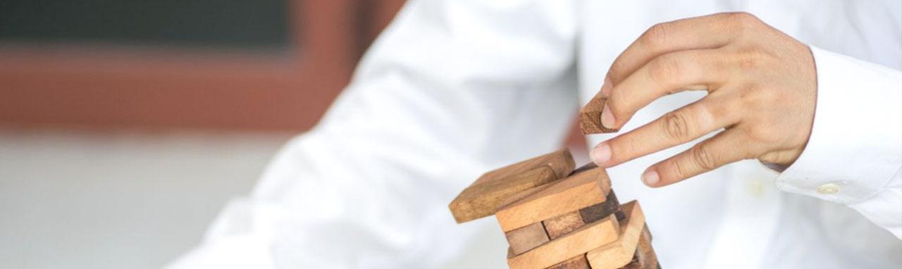 Un homme en chemise fait tombé une pyramide de morceau de bois