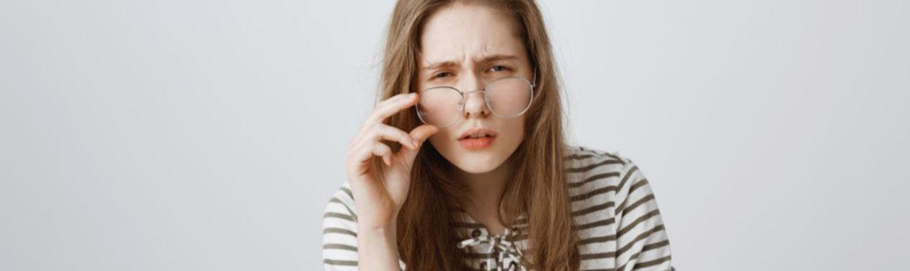 Une femme dos à un mur porte ses lunettes sur le bout de son nez d'un air interrogateur