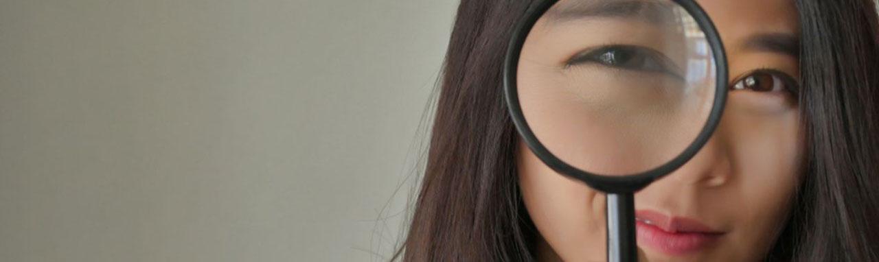 Photo d'une femme tenant une loupe devant son œil droit