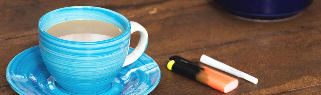 une tasse de café au lait, un briquet, une cigarette et un cendrier sont posé sur une table en bois