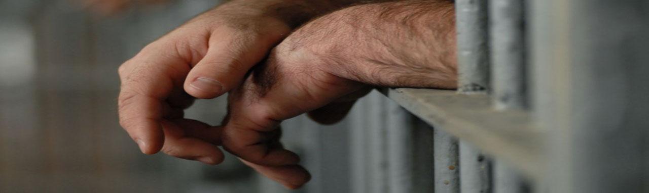 Gros plan sur les mains d'un homme qui dépasse d'une cellule de prison