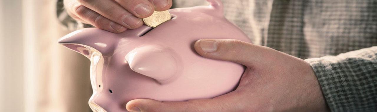 Un homme glisse une pièce dans la fente d'une tirelire en forme de cochon
