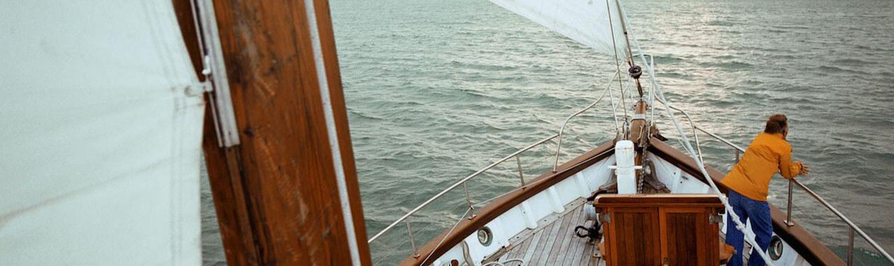 Photographie de la mer prise depuis le mat centrale d'un voilier. On voit un homme à la proue.