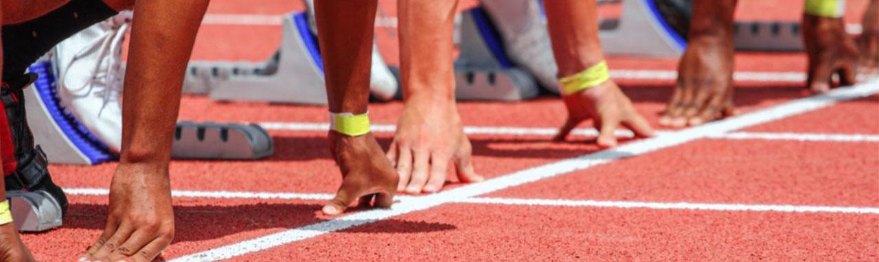 Gros plan sur les mains d'athlète s'apprétant à prendre le départ d'une course d'athlétisme