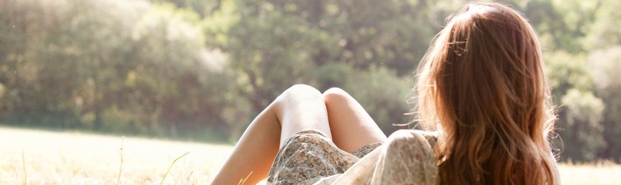 Une femme en robe est allongé dans l'herbe face à une forêt