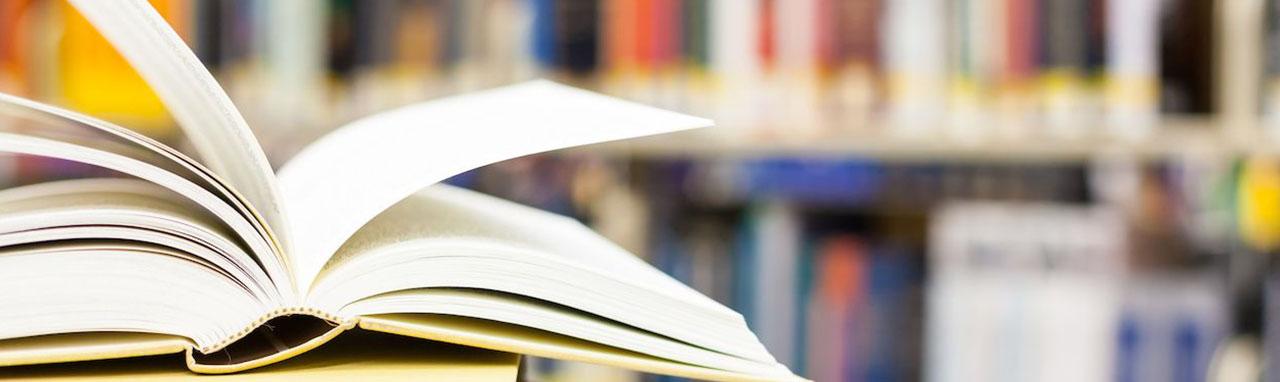 Des livres sont ouverts et posé sur une table devant une bilbliothèque