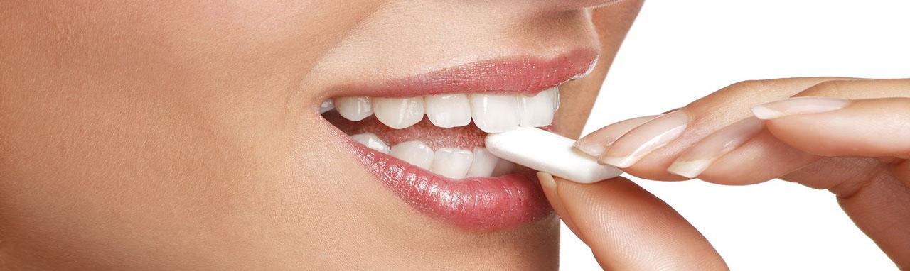 Une femme porte à sa bouche une gomme à macher à la nicotine