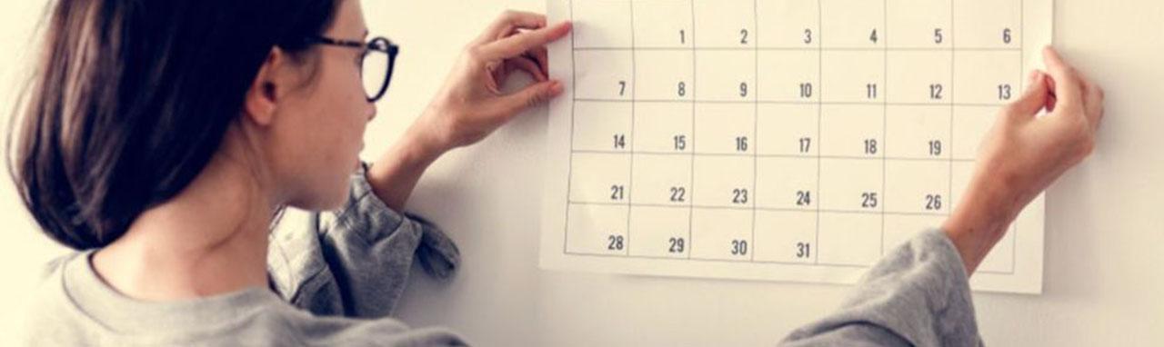 Une femme accroche un calendrier sur un mur blanc