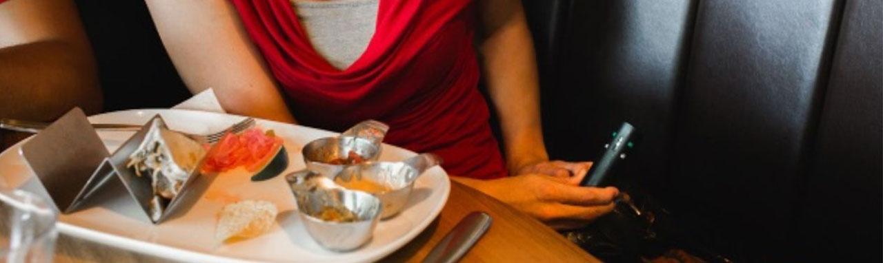 Une femme dans un restaurant prend un spray dans son sac