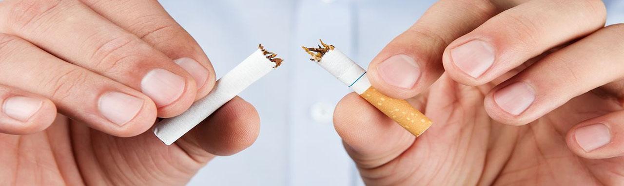 Un homme en chemise tient une cigarette brisée entre ses doigts