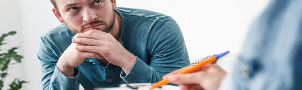 Un homme écoute un médecin qui tient un bloc note parler