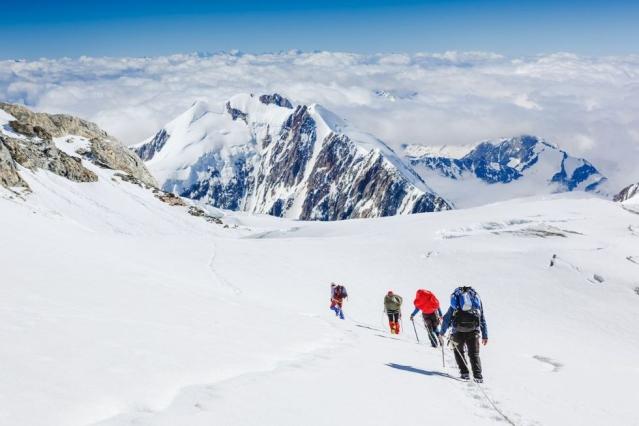 Une équipe de 4 personnes marchent à travers une plaine enneigée face à une montagne