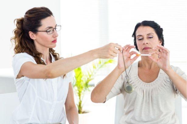 Un femme tient une cigarette comme pour la briser tandis qu'une autre femme agite un pendule devant elle