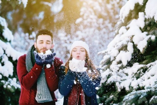 Un couple se tient dans une forêt enneigée et souffle sur un petit tas de neige dans leurs mains