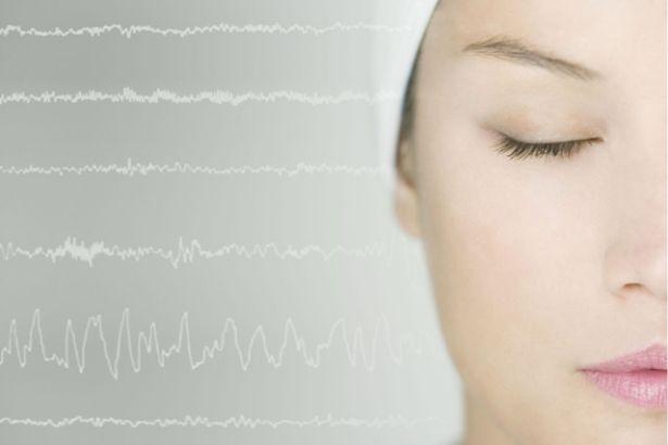 Gros plan sur le visage d'une femme les yeux fermés, sur la gauche une représentation d'un electro-encéphalogramme