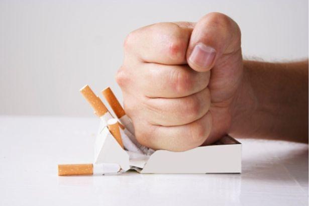 Un poing écrase un paquet de cigarette blanc sur un fond blanc
