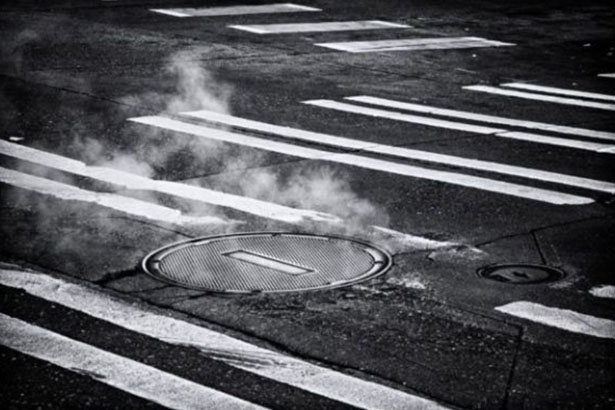 Une bouche d'égout fumante au milieu d'une route