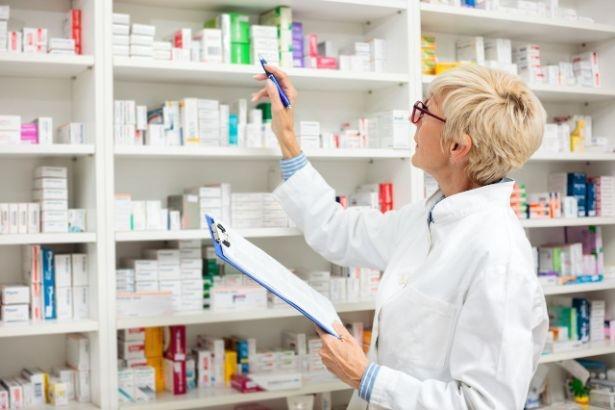 Une pharmacienne tenant un bloc note se tiens face à des étagères remplies de médicament