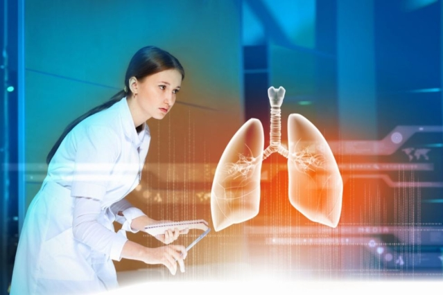 Une scientifique devant un bureau observe une paire de poumon modélisé en 3D