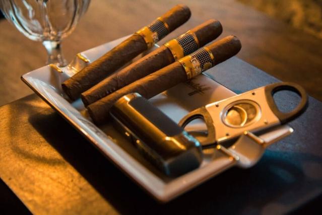 Trois cigares posés dans un récipient avec un coupe-cigare et un briquet sur une table en bois