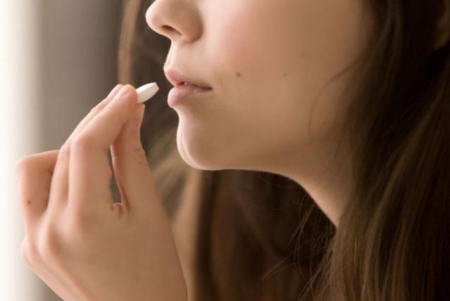 Une femme porte un comprimé à sucer à sa bouche