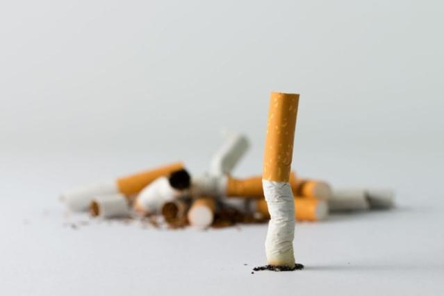 En arrière plan, un petit tas de cigarette ecrasées et une cigarette écrasée au premier plan