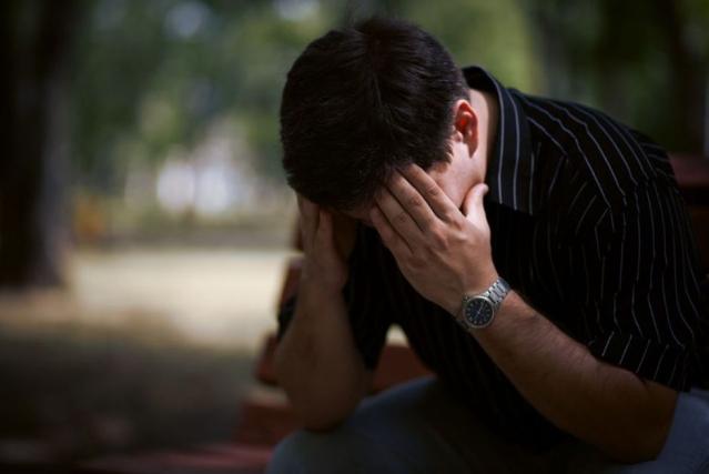 Un homme est assis dans un par cet tient sa tête entre ses mains pour montrer qu'il à des difficultés de concentration