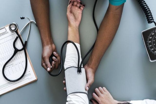 Une personne se fait mesurer sa tension par un médecin à l'aide d'un appareil