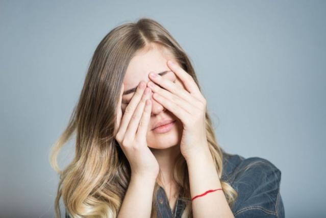 Une femme se tient la tête entre les mains sur un fond gris