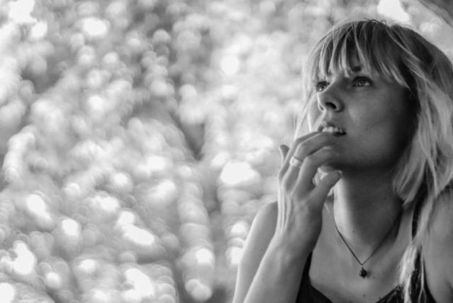 Photo en noir et blanc d'une femme pensive avec la main sur la bouche