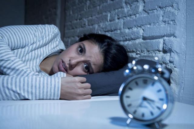 Une femme est allongé dans un lit devant un réveil indiquant 4h du matin