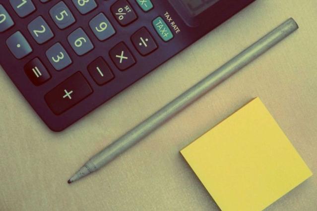 Une calculatrice, un stylo et un bloc de post-it sont posés sur un bureau