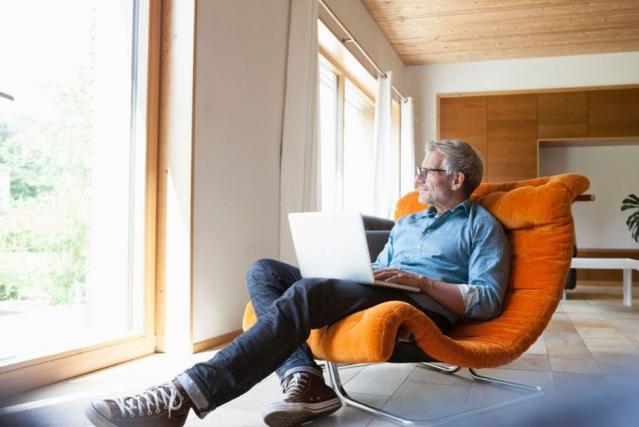 Un homme mûr se tient allongé dans un fauteuil avec un livre dans une maison design