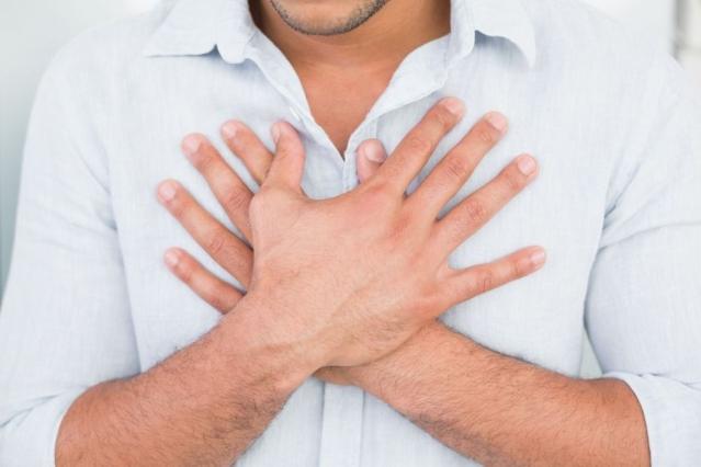 un homme en chemise claire se tient la poitrine avec les deux mains croisées.
