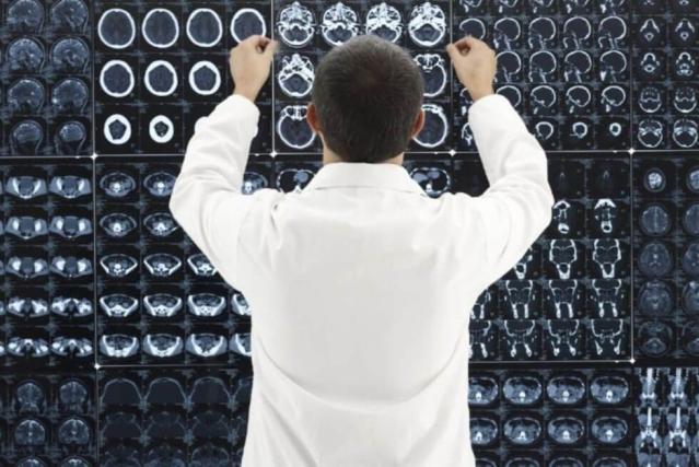 Médecin de dos devant une multitude de radiographie