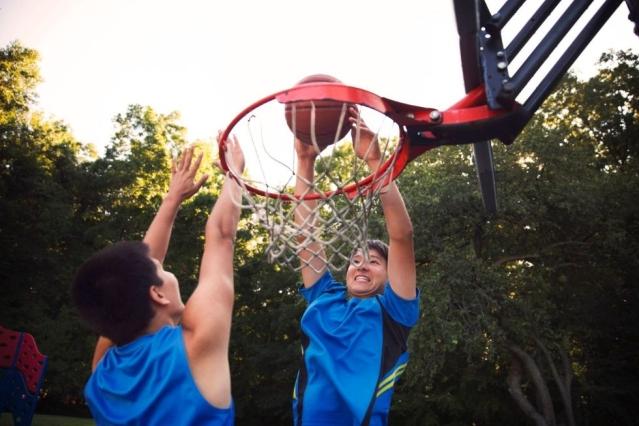 Deux hommes sautent pour attraper une balle au dessus d'un panier de basket