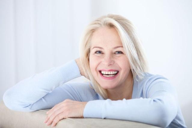 Une femme mûre souries en s'appuyant sur le dossier d'un canapé