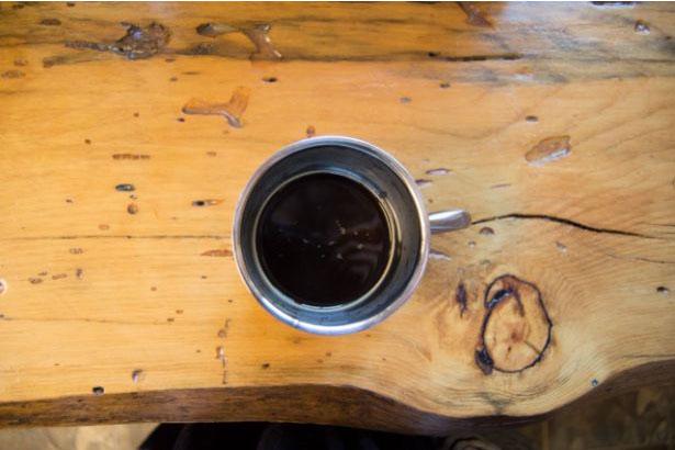 Une tasse de café noir sur une table en bois