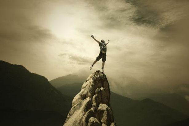 Un homme se tient debout en haut d'un pic rocheux, l'air victorieux