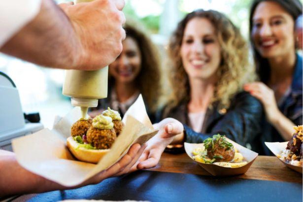 Un groupe de trois femmes se tienne devant un homme entrain de préparer un sandwich au falafels