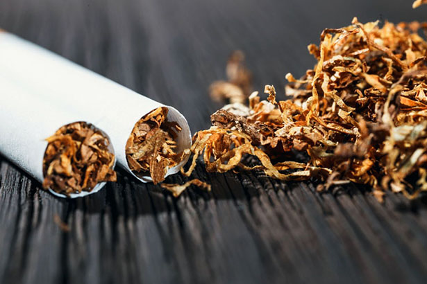 Une cigarette cassée en deux avec du tabac renversé à coté, sur une table en bois