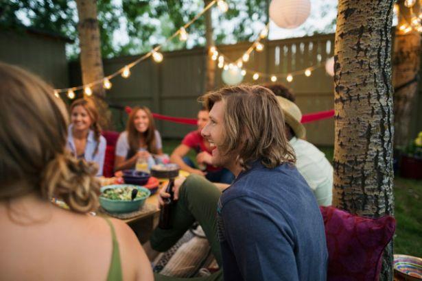 Un groupe de jeunes adultes se tient sur une terrasse illuminée par des guirlandes lumineuses