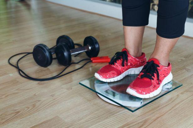 Une femme se pèse avec ses chaussures de sport, à coté d'elle est posé du matériel de fitness