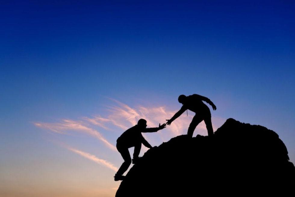Une personne aide une autre personne à atteindre le haut d'une montagne en la tenant par le bras