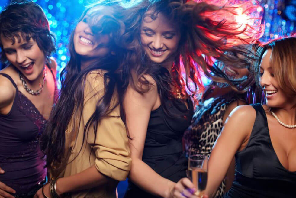 Un groupe de quatre jeunes femmes dansent dans une boite de nuit