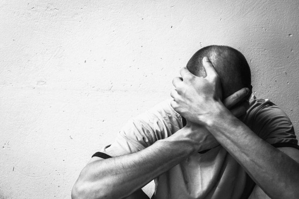 Un homme se tient assis dos à un mur et se tient la tête pour signifier la dépression, en noir et blanc