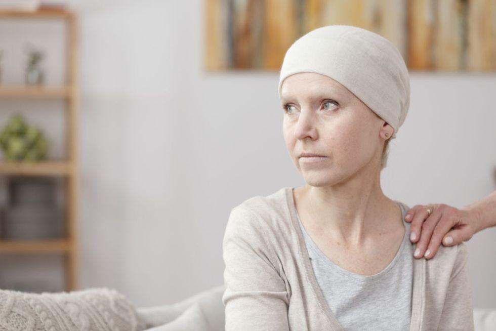 Une femme atteinte d'un cancer est assise sur un canapé, une main est posée sur son épaule comme pour la réconforter