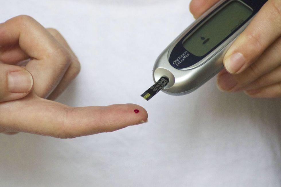 Gros plan sur le doigt d'une personne diabétique entrain de tester sa glycémie en prélevant une goutte de sang